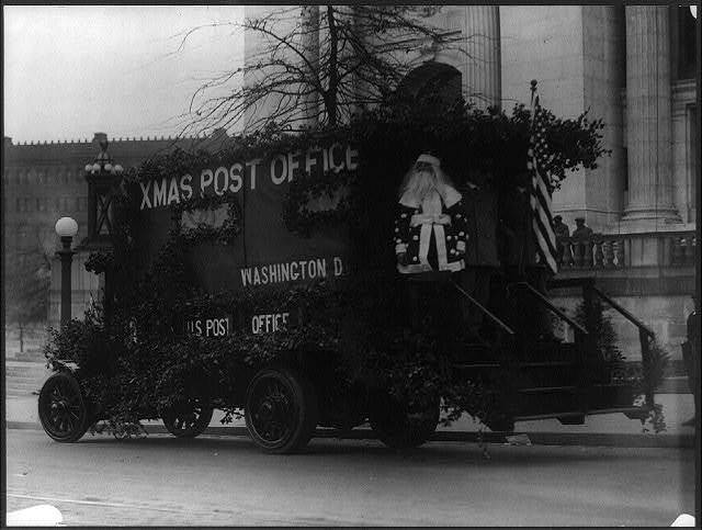 [Santa Claus standing on back of Washington, D.C., Post Office truck, decorated with branches and American flag]