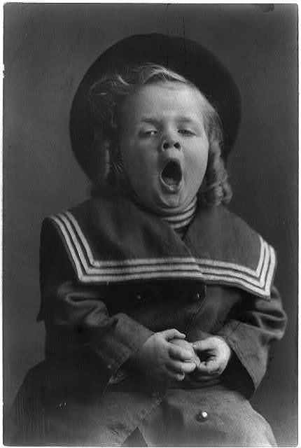 [Small boy with long hair wearing hat and sailor coat yawning]