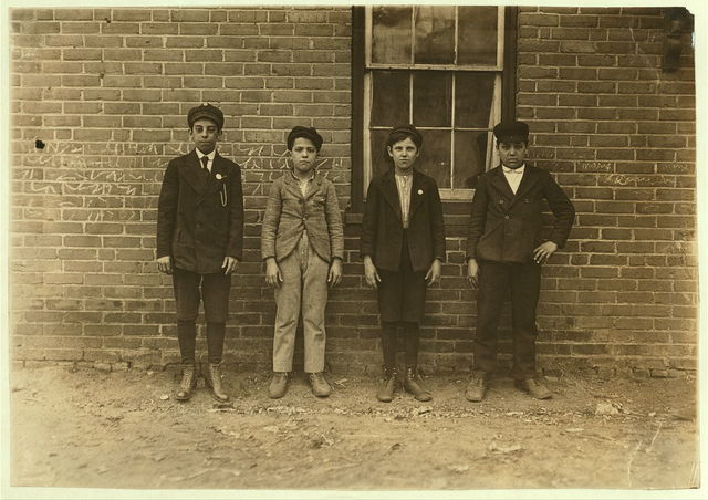 Sweepers & mule-room boys in Royal Mill, River Point, R.I. Boy left hand end, Manuel Mites has been in mill 2 years. Clinton Silvey and Louis Perry (centre boys) have been in mill one year and said they are now 12 years old. Boy on right hand Manuel Silvey been in mill 1 year. (They could not speak English).  Location: River Point, Rhode Island.