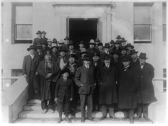 [The Osage Council, with other Osage Indians, who came to Washington in connection with gas and mineral rights on the Osage Nation in Oklahoma. Commissioner of Indian Affairs Cato Sells, Assistant Commissioner E.B. Meritt and Superintendent of the Osage Nation J. George Wright are in foreground]
