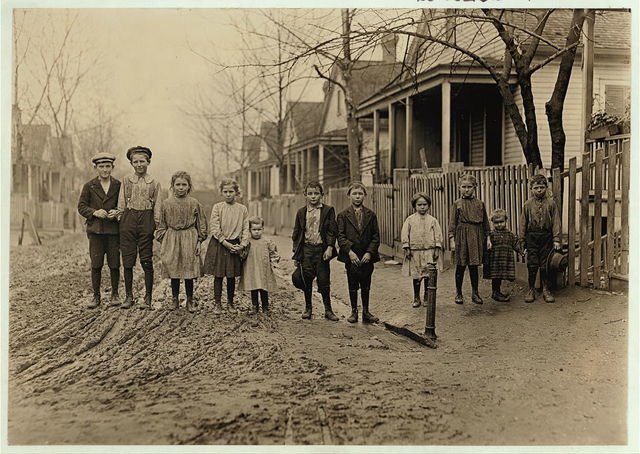 """The Rising Generation, Gregtown, Augusta, where the hands in King Mill live. """"Worst part of Augusta."""" Secretary of Associated Charities said. Boy with cap (left hand end) Willie Crappse in mill work for 4 years. next Jimmie Reese, 2 years in mill.  Location: Augusta, Georgia."""