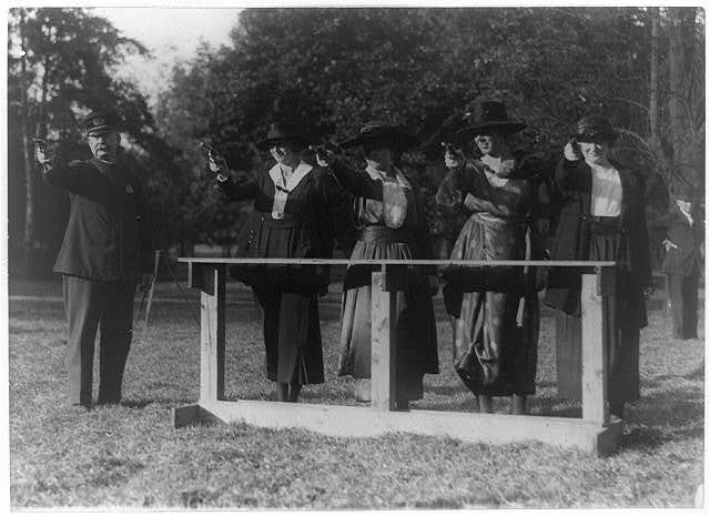 """Training a policewoman--target practice under the direction of Inspector Cross of the police department--Inspector Cross demonstrates the correct way to hold a """"gat"""""""