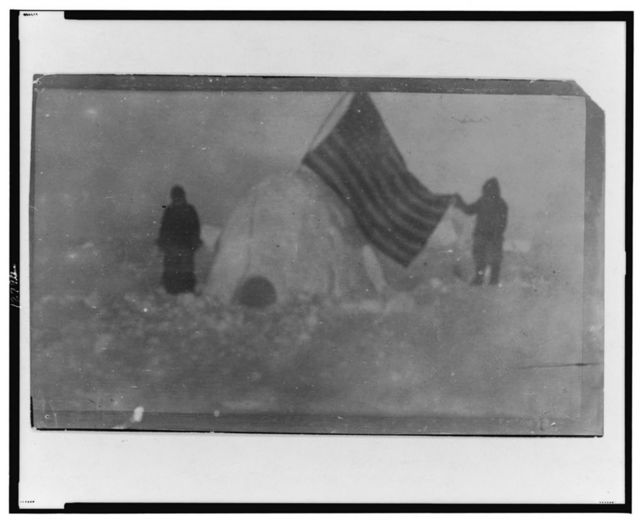 [Two members of Frederick Cook's expedition, with U.S. flag stuck in igloo, at expedition camp site, North Pole]
