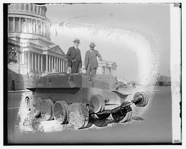 [Two persons standing on tank outside Capitol building]