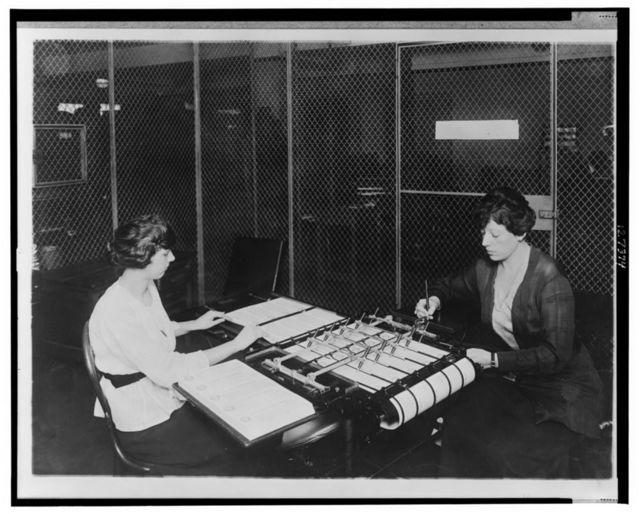 [Two women using check signing machine which signs checks issued by the War Risk Bureau, Washington, D.C.]