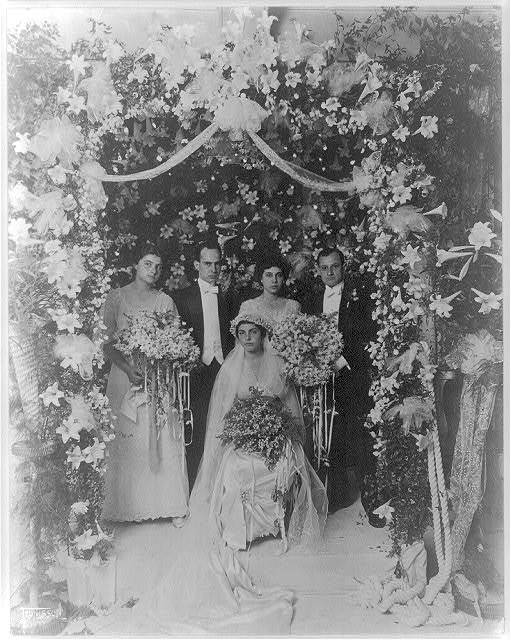 [Wedding party inside arbor of flowers]