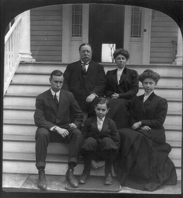 [William Howard Taft, seated, facing front, with family on porch steps]