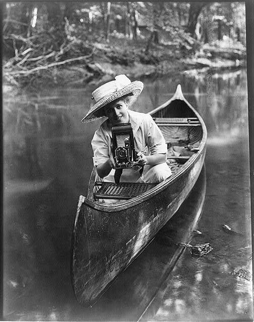 [Woman in canoe pointing camera]