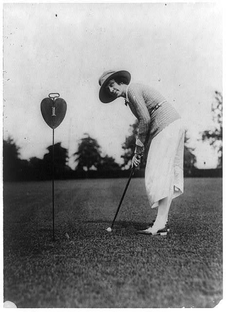 [Woman swinging at golf ball close to hole, Washington, D.C., area]