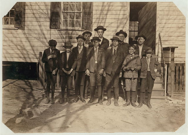 Workers in Bibb Mill #1, Macon, Ga. Boy on right on right hand end, Burdick Collins, 2 years in mill work. Next, Scoven Preston, 1 year in mill work. Next, Charlie Benson, 4 years in mill work. Next, Mason Matheson. Next, Robert Collins. Next, Leo House, 4 years in mill work. Next, Frank Leslie. Father in background. Witness S.R. Hine.  Location: Macon, Georgia.