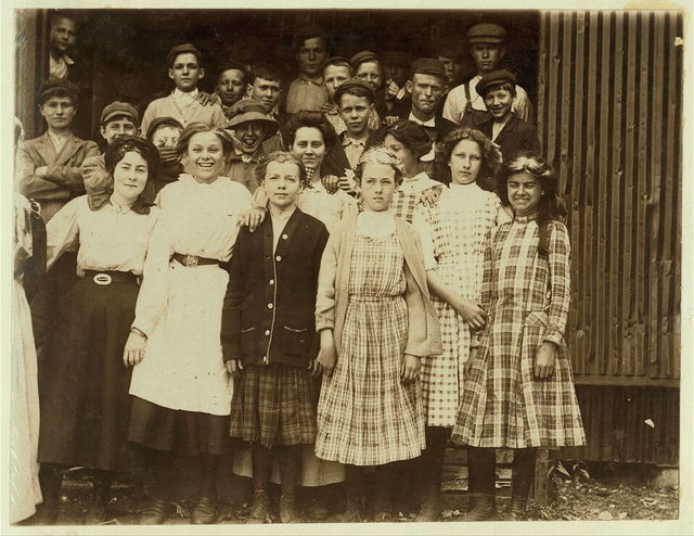 "A group of girl workers at Greenabaum's Cannery, Seaford, Del. The girls in the front row are ""cappers"" and ""layers."" They range from 6 years of age up. Working from 10 to 12 hours per day. Among the unguarded belting machinery of the Cannery.  Location: Seaford, Delaware."