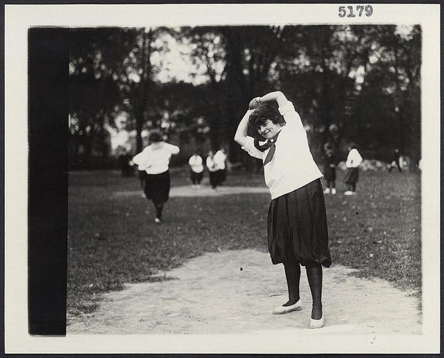 [A women's softball baseball game showing a woman on the pitcher's mound about to pitch the ball]