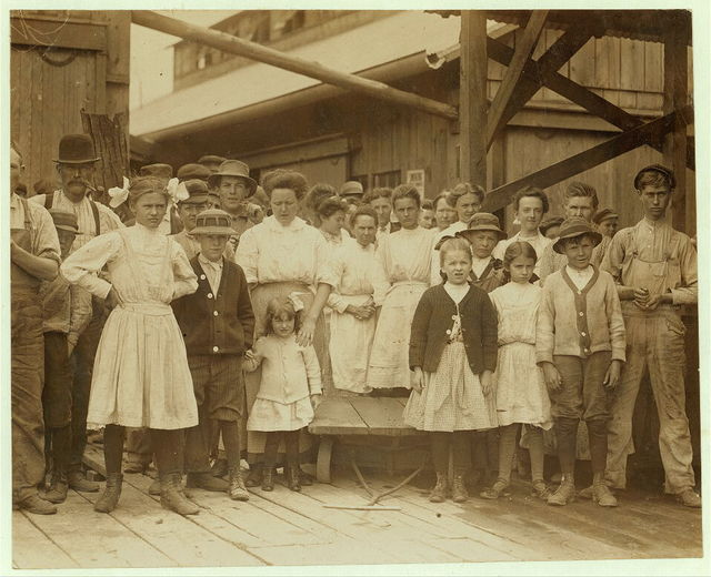 All are workers in the Ross Cannery, Seaford, Del. The smallest girl seen in the picture was at work 8 o'clock in the morning of the investigation and was seen the same night at 9 P.M. During one visit of the investigators about 2 P.M. she was absent. She appears to be about 5 years of age and works irregularly in the cannery exposed to the dangers of the unprotected belting. Her mother works beside her.  Location: Seaford, Delaware.