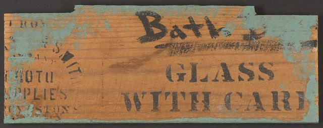 "[Board from a wooden shipping crate with stencil ""Glass With Care"" and hand lettering ""Bath B(?)""]"