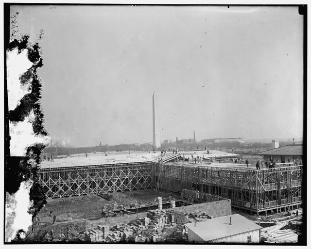 [Building under construction, Washington Monument in background]