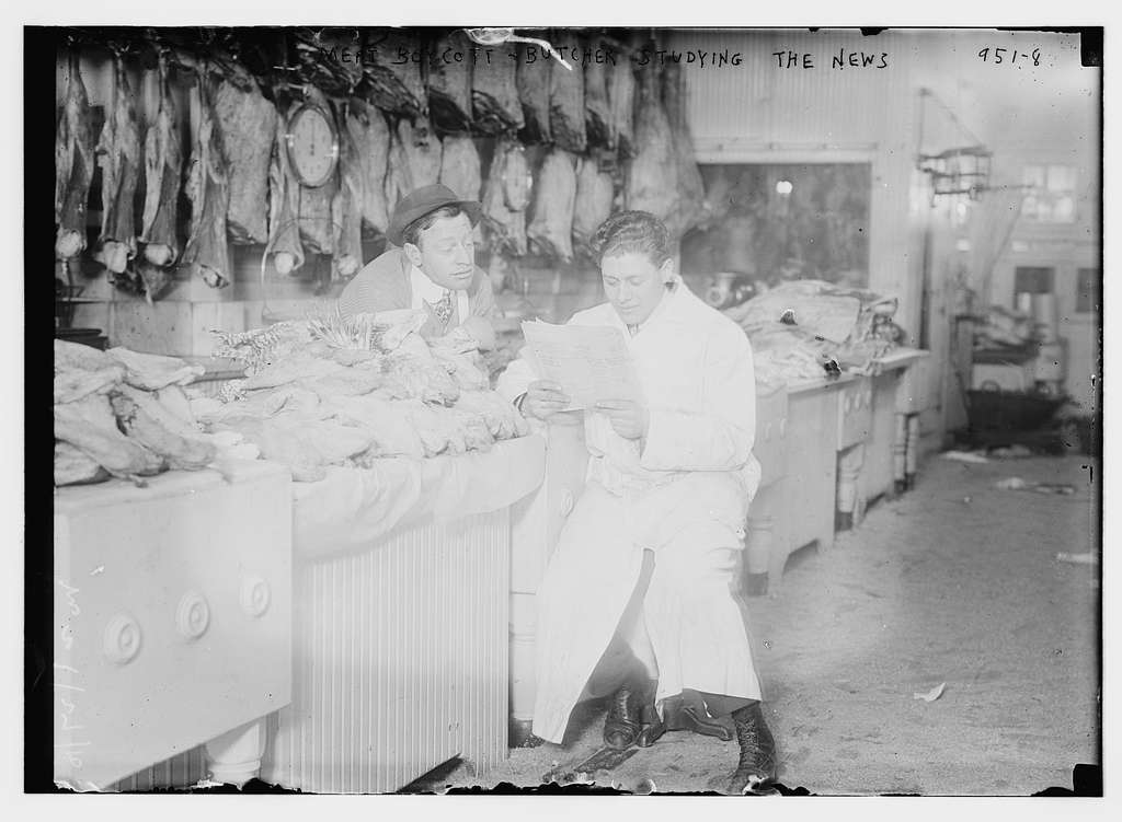 Butchers read newspaper at the counter full of meat during meat boycott