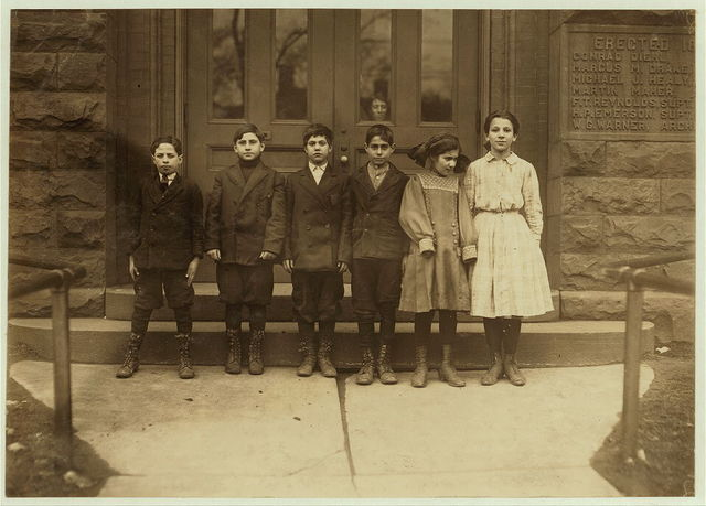 Cannery children in School # 2 Buffalo, N.Y. Two boys on left end work nights. Cosmus Laduca, 11 years old last summer. Worked on beans and corn in sheds, So. Dayton, N.Y. Frances Seinta, 13 years old last summer. Worked on beans in factory, Barker, N.Y. $1.50 a day. Lost 10 weeks school. Is a repeater. Mary Sciolino, 10 years old last summer stringing beans in sheds, Barker, N.Y. Salvatore Dicarlo, 11 years old last summer. Working on beans and corn until 9 P.M., sometimes, Albion, N.Y. Calegevo Mondo, 12 years old last summer. Husking corn, stringing beans, sticking apples on machine, Wilson , N.Y. Lost 11 weeks. Is a repeater in school. Cosmus Guarino, 12 years old last summer. Worked on beans and corn in sheds, Albion, N.Y. sometimes until 11 P.M. Also dropped cans. Lost 11 weeks school. Is a repeater.  Location: Buffalo, New York (State)