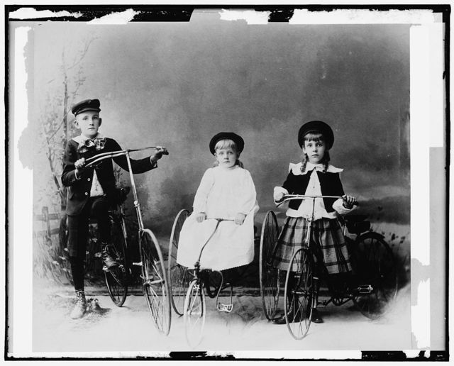 [Children posed with bicycle and tricycles]