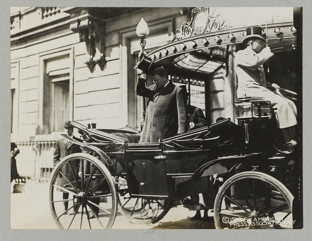 [Col. Theodore Roosevelt standing in carriage and saluting crowd when leaving The Hague from Des Indias Hotel]