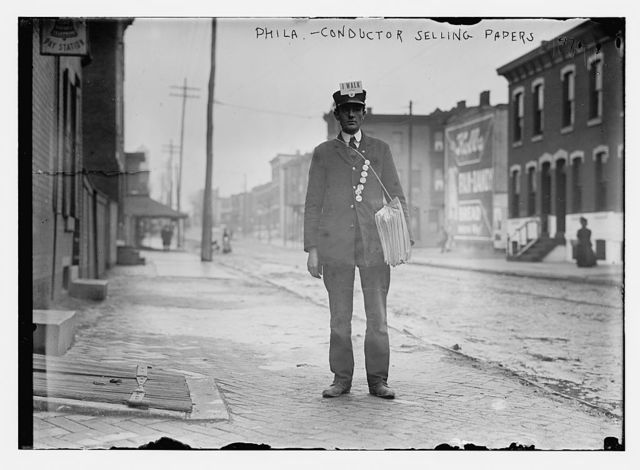 Conductor from transit system selling papers on street, Philadelphia
