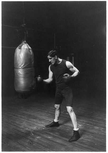 Corbett punching the bag to get in condition to handle Jeffries for the championship fight. First photos taken with gloves in five years