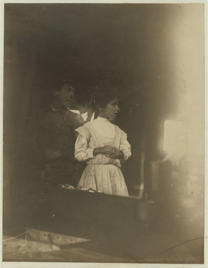 Daisy Langford, 8 years of age, working at the capping machine in Ross's Cannery, Seaford, Del. (see photo [crossed out]) Edward F. Brown, Investigator.  Location: Seaford, Delaware / Photo by Lewis W. Hine.