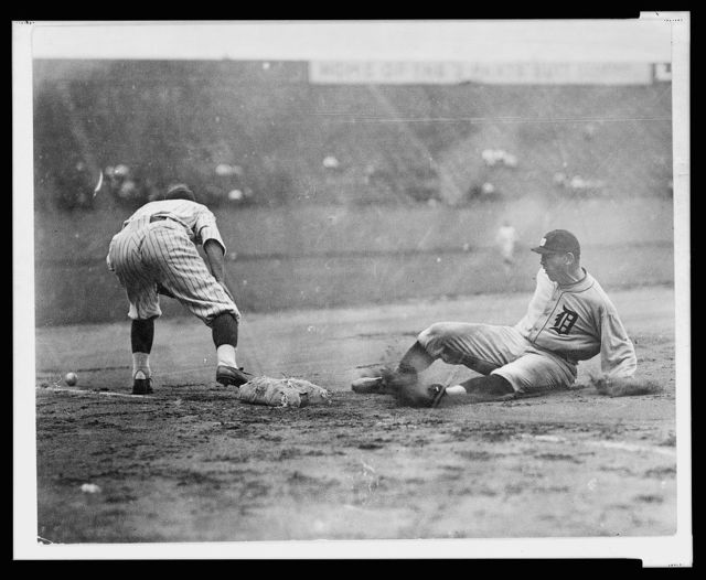 [Detroit ball player slides safely into third base as fielder reaches to the left for ball on the ground during baseball game]
