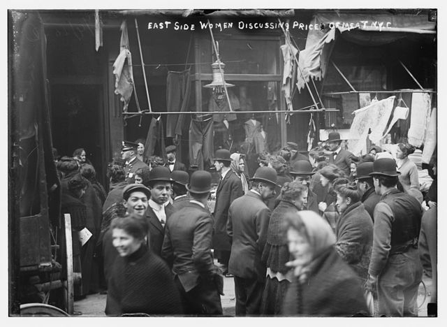 East side crowd discussing price of meat in front of shops, New York