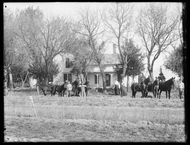 Family and horses in front of J.H. Salter's house, northeast of Shelton, Nebraska.