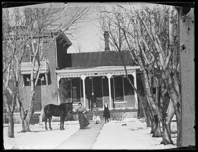 Family, horse, and dog in front of a house in Kearney, Nebraska