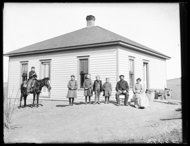Family in front of one-story frame farmhouse, Buffalo County, Nebraska.