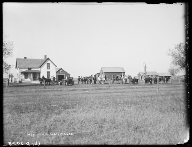 Family posed with their automobile n front of the  W.M. Schlattman home, northeast of Kearney, Buffalo County, Nebraska.