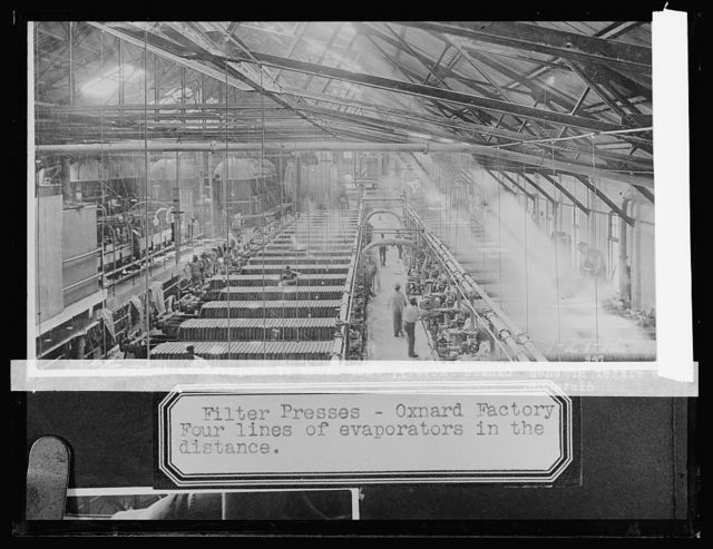Filter presses, Oxnard, [California], factory, four lines of evaporators in the distance