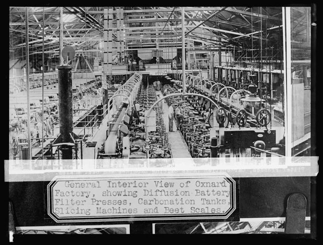 General interior view Oxnard, [California], factory showing diffusion battery filter presses, carbonation tanks, slicing machines, and beet scales