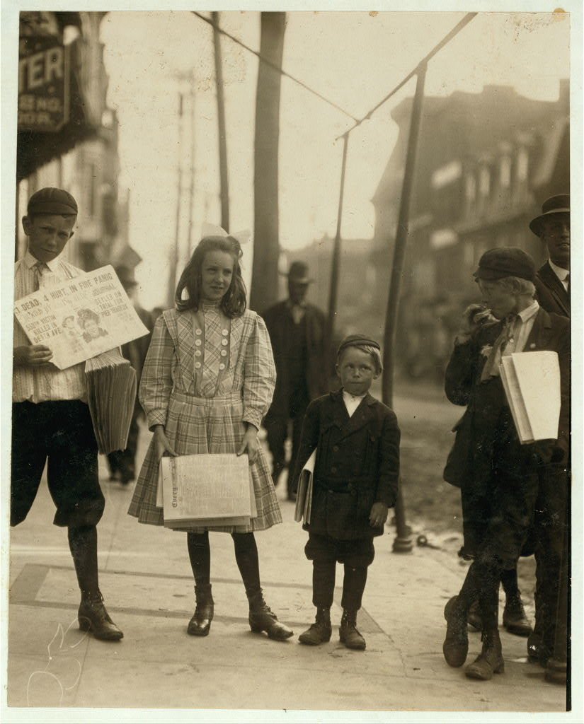 Girl and boys selling papers. Edward F. Brown, Investigator.  Location: Wilmington, Delaware / Photo by Lewis W. Hine.