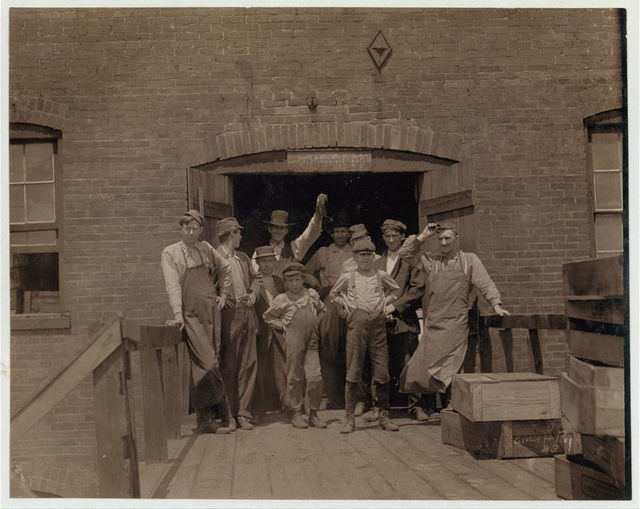 Group of Glass Workers in Shop 6, Illinois Glass Co. The smallest boy is Polish and does not understand English (Illiterate) I saw him at work just before 1 P.M.  Location: Alton, Illinois.