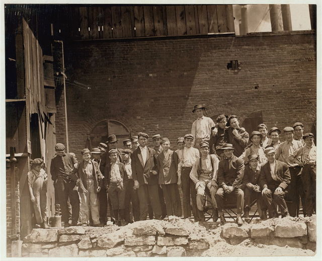 Group of glass workers Shops 6 & 7, Illinois Glass Co. 12:45 P.M. Even the tiny chap on left end of photo was working. He is a Polish boy who cannot understand English. I saw him at work just before 1 P.M.  Location: Alton, Illinois.