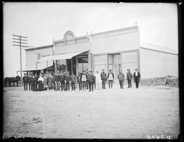 Group of people gathered on street in front of F.J. Trindle Store, Oconto, Custer County, Nebraska.