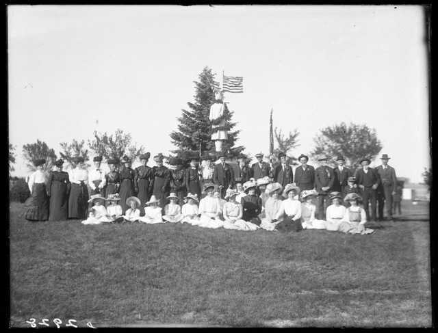 Group of women, men, and children assembled on lawn of the cemetery at Gibbon, Nebraska.