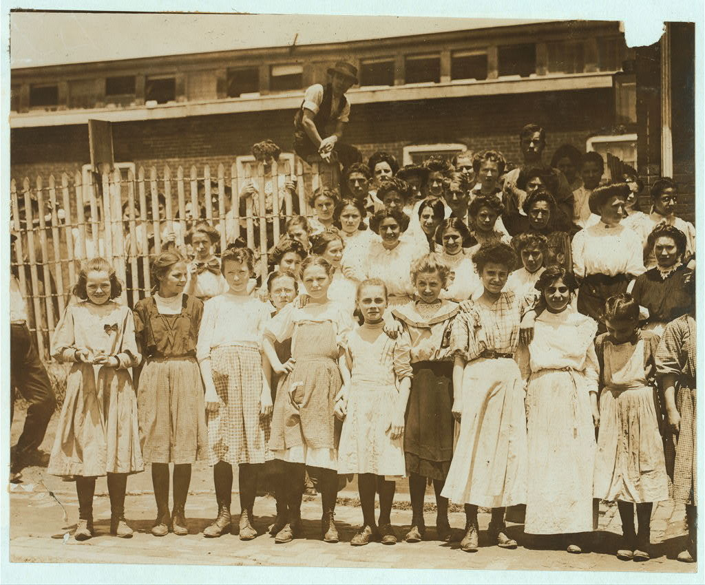[Groups of girls workers at the gate of the American Tobacco Co., Wilmington, Delaware, noon period, May 24, 1910. Young girls obviously under 14 years of age, who work about 10 hours a day every day except Saturday. Investigator, Edward F. Brown.]  Location: Wilmington, Delaware / Photo by Louis [i.e. Lewis] W. Hine, May, 1910]