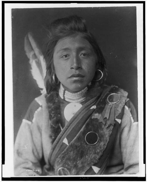 [Kashhila--Wishham. Male Chinookan Indian, head-and-shoulders portrait, facing front, with pompadour, fur wrapped braids, bead choker around neck, beaded buckskin shirt, fur sash over left shoulder]