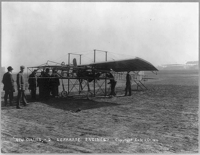 "[Men inspecting airplane - ""New Curtiss - 2 separate engines""]"