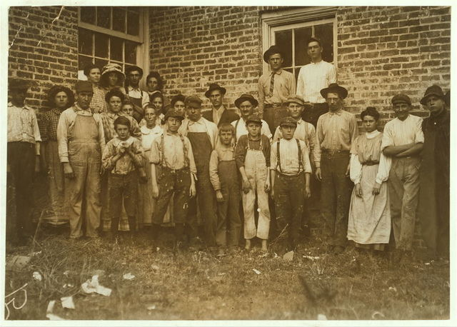 Most of the workers in Munford Cotton Mills. The smallest boy, in middle, a frail anaemic youngster, said he had been doffing over a year. Said he was 12 years old, but I doubt it. The other small boy, on left, is a spinner, runs four sides, been working there two years. Said he was 12; - but --?.  Location: Munford, Alabama.