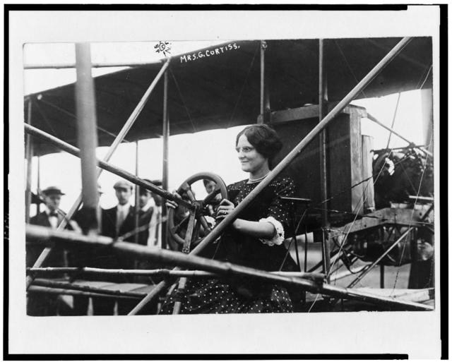 [Mrs. Glenn Curtiss at the controls of an airplane]