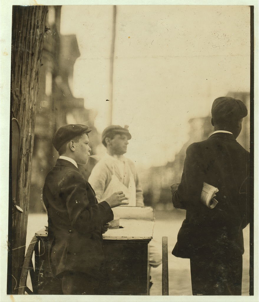 Newsboy smoking cigarets [sic] on 4th & Orange Sts. Investigator, Edward F. Brown Wilmington, Delaware.  Location: Wilmington, Delaware / Photo by Louis [i.e. Lewis] W. Hine, May, 1910.
