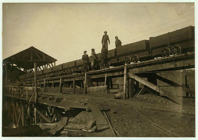 """On the tipple at the Bessie Mine, Sloss-Sheffield Steel & Iron Co. These young boys work around and on these coal cars, loaded and empty, while they are running at full speed. It is dangerous. One of these boys said, """"Ain't hardly a day goes by that someone don't get pinched or hurt."""" """"I got my leg jammed a while ago and was laid up a week.""""  Location: Bessie Mine, Alabama."""