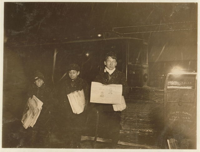 """Selling on Main Street, 9:30 P.M. Left to right: Joseph Magus, 10 years old, 80 Melody St. Guy Casacali, 12 years old, 31 Maple St. Morris Stein, cripple, 14 years old, 53 Sullivan St. Asked policeman on corner where they were selling, how late they stayed out at night. He answered evasively; """"Ain't supposed to be out after nine o' clock.""""  Location: Rochester, New York (State)"""