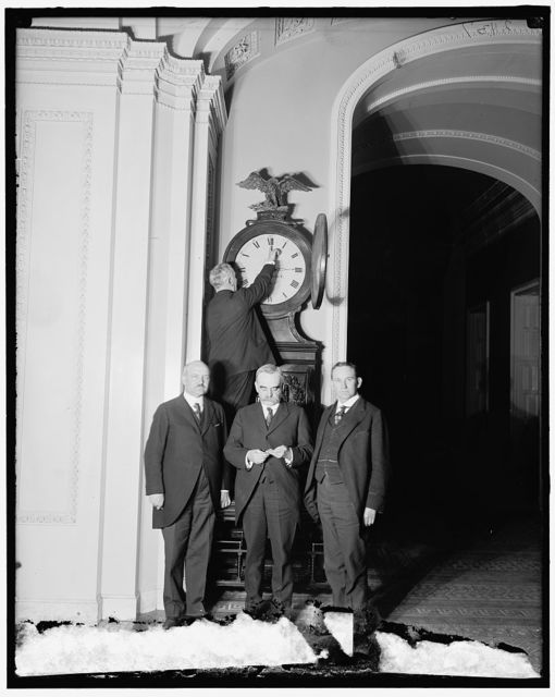 [Senate Sergeant at Arms Charles Higgins turns forward the Ohio Clock for the first Daylight Saving Time, while Senators William Calder (NY), William Saulsbury, Jr. (DE), and Joseph T. Robinson (AR) look on, 1918. U.S. Capitol building, Washington, D.C.]