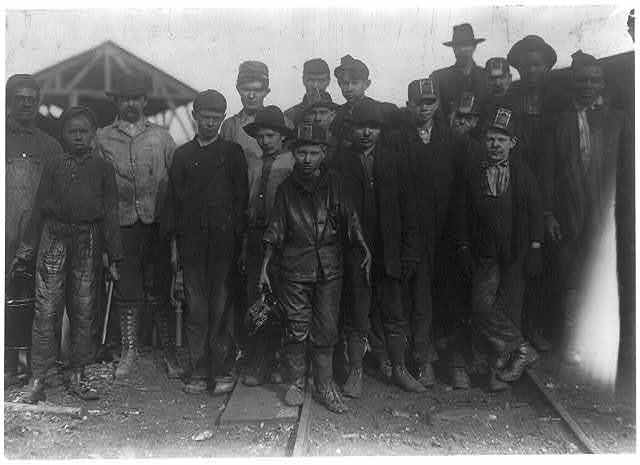 """Shorpy Higginbotham, a """"greaser"""" on the tipple at Bessie Mine, of the Sloss-Sheffield Steel and Iron Co. Said he was 14 years old, but it is doubtful. Carries two heavy pails of grease, and is often in danger of being run over by the coal cars.  Location: Bessie Mine, Alabama."""