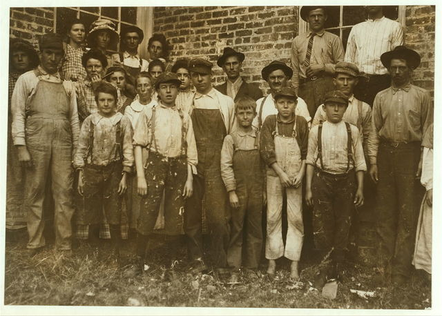 Some of the workers in Munford Cotton Mills. Smallest boy, in middle, a frail anaemic youngster, said he had been doffing over a year. Said he was twelve, but I doubt it. Other small boy, on left, spinner, runs four sides, been working there two years.  Location: Munford, Alabama.